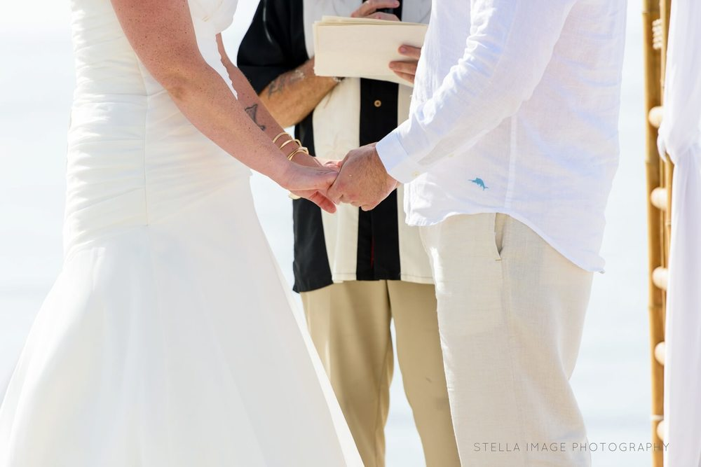Bride and groom hold hands at the alter
